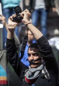 A photojournalists with his mouth tapped holds up his camera as he demonstrates with fellow colleagues in front of the journalist's syndicate in Cairo against repeated attacks on members of the press in Egypt on April 4, 2014. (AFP File Photo)